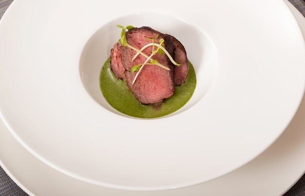 Beef with green sauce on a white dish