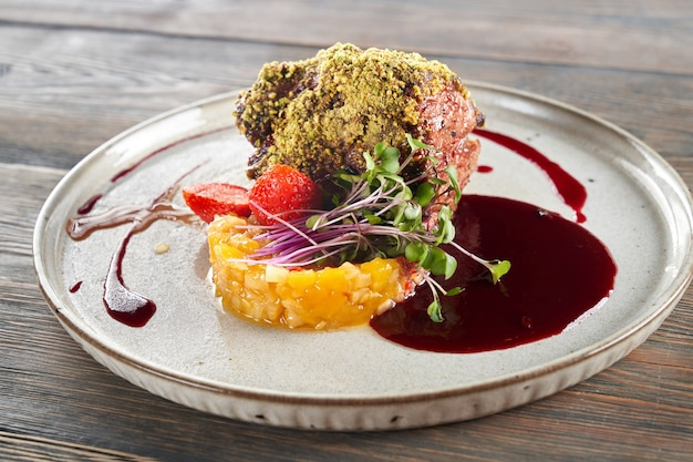 Beef with pistachio topping served with fruits and berries