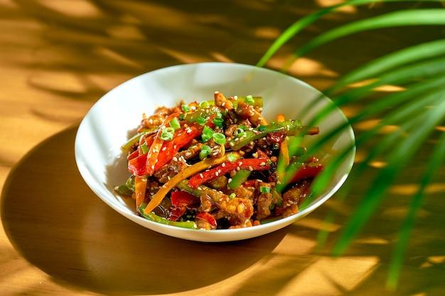 Вок из говядины в кисло-сладком соусе с овощами и сычуаньским перцем в миске. китайская кухня