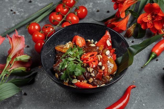 쇠고기 냄비. 젓가락, 돌 슬레이트 배경 요리와 함께 중국 주철 냄비에 전통적인 중국 몽골 쇠고기 볶음 튀김. 상위 뷰, 복사 공간.