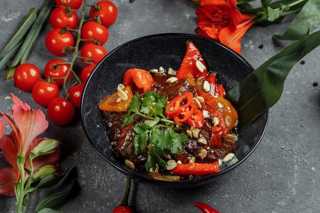 牛肉の中華鍋。伝統的な中国のモンゴル牛肉を中国の鋳鉄鍋で箸、石のスレートの背景を調理で炒めます。