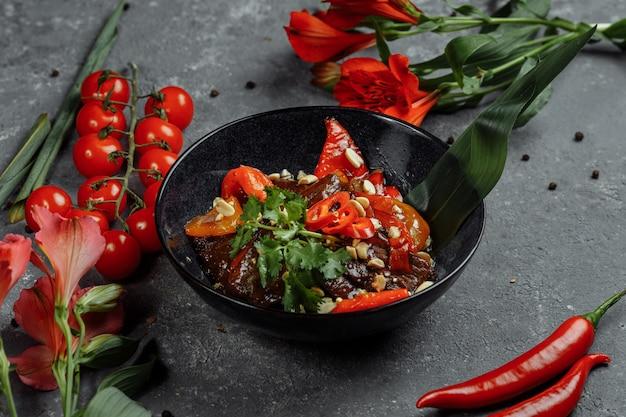 牛肉の中華鍋。伝統的な中国のモンゴル牛肉を中国の鋳鉄鍋で料理用箸で炒める