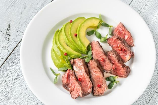 Бифштекс, украшенный красным перцем и украшенный ломтиками авокадо