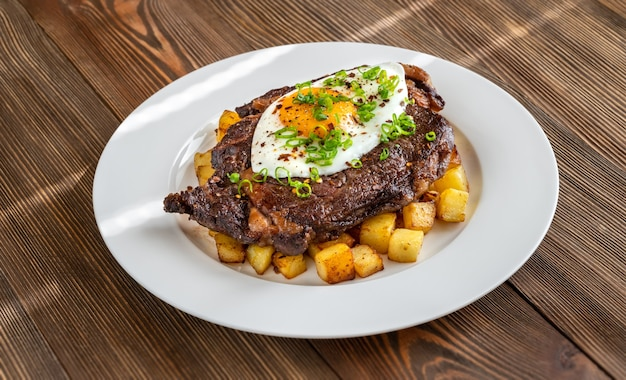 Beefsteak with fried egg and potato flat lay