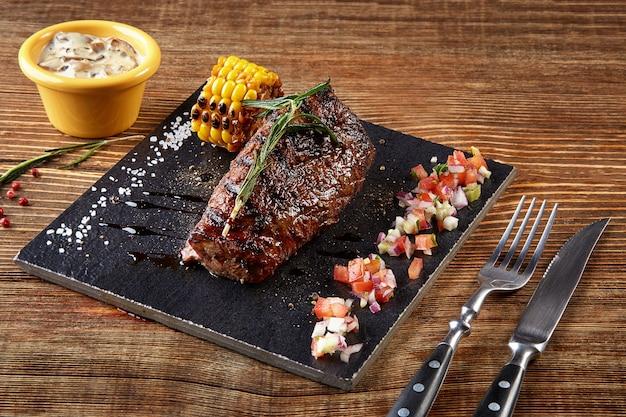 블랙 보드에 구운 옥수수와 나무 테이블에 버섯 소스를 곁들인 비프 스테이크