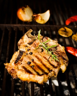 Beefsteak with spices and vegetables on grill