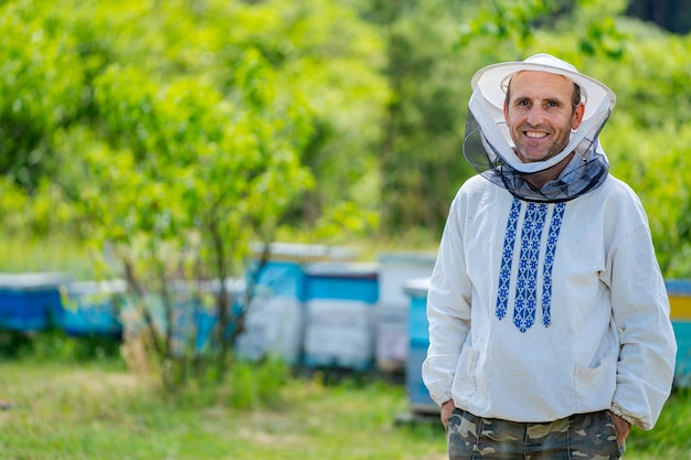 夏の日の養蜂場の養蜂家。養蜂場で働く男。養蜂。養蜂の概念。