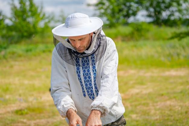 Пчеловод на пасеке в летний день. человек, работающий на пасеке. пчеловодство. концепция пчеловодства.