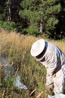 Пчеловод готовит свое оборудование в поле. скопируйте пространство.
