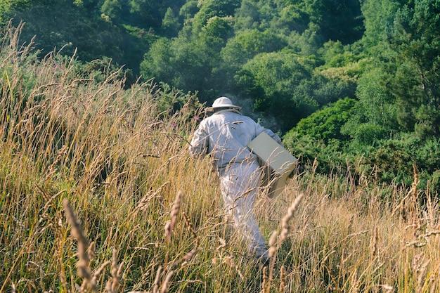 Пчеловод идет по полю со своим рабочим оборудованием. скопируйте пространство.