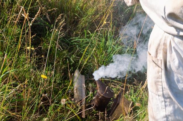 Пчеловод со своим оборудованием в поле. скопируйте пространство.