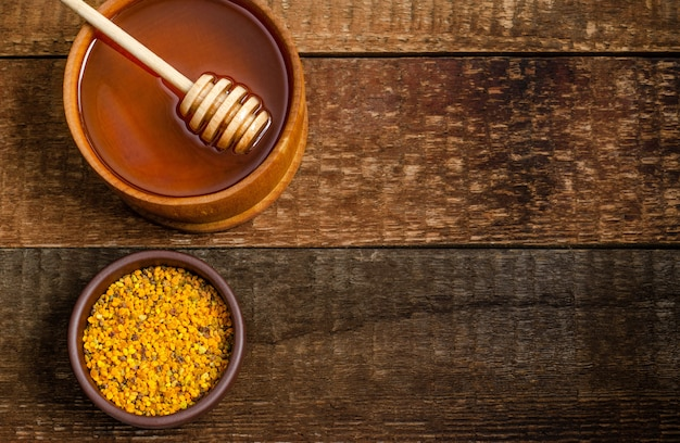 Beekeeping products honey and pollen on a wooden background.
