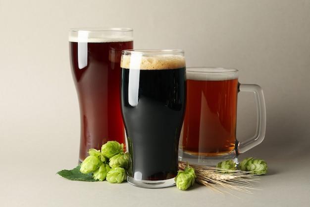 Пиво и зеленый хмель на сером фоне
