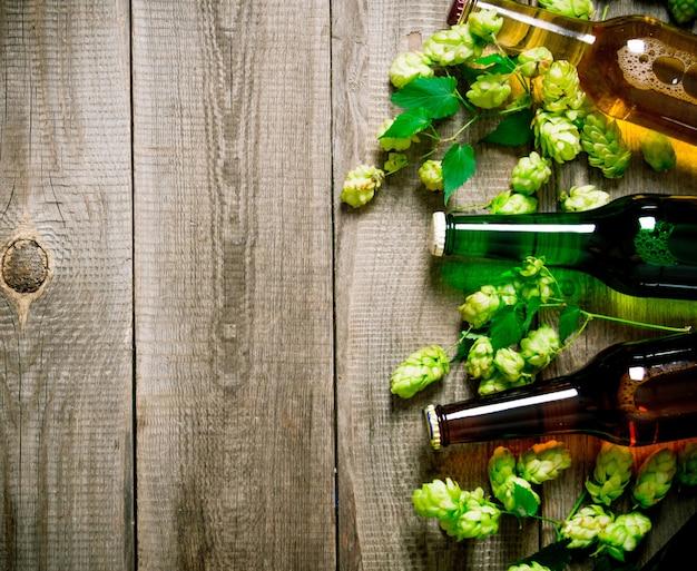 Пиво и зеленый хмель на деревянном столе. вид сверху
