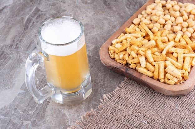Пиво и тарелка крекеров и гороха на мраморной поверхности. фото высокого качества