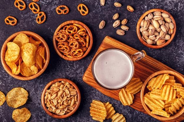 Пиво и различные закуски в мисках с картофельными чипсами, орехами и кренделями.