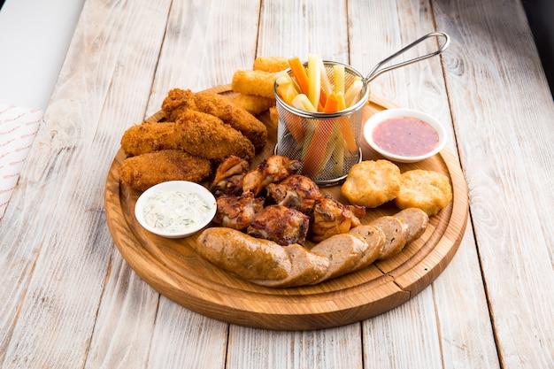 Блюдо пивных закусок на деревянной доске