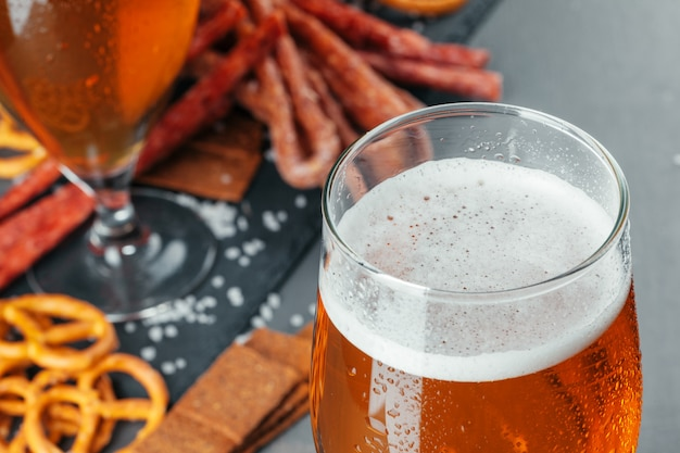 Beer and appetizing beer snacks set. table with mug of beer, wooden board with sausages