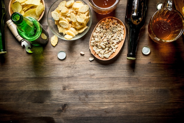 Beer and an assortment of different types of snacks. on wooden table