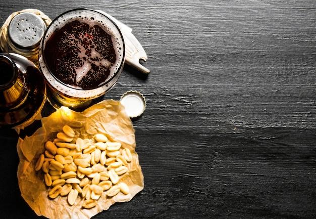 Пивной фон. пиво с арахисом на черном деревянном столе