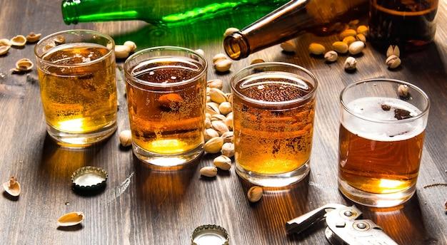 ビールの背景。木製のテーブルにピスタチオと4つのビール。