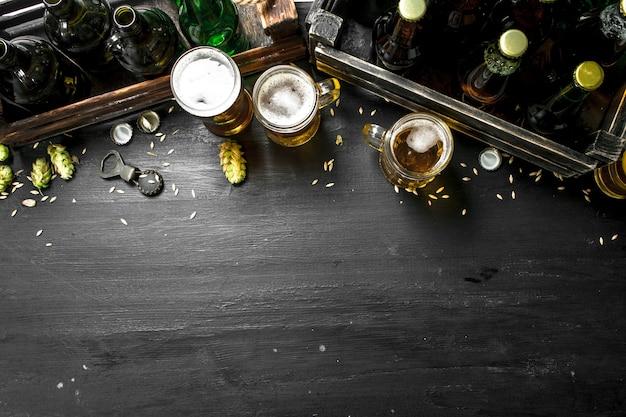 Пивной фон. свежее пиво и ингредиенты. на черной доске.