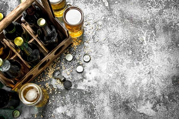 Пивной фон. свежее пиво в очках и старой коробке. на деревенском фоне