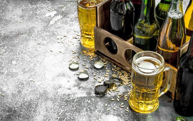 ビールの背景。グラスに新鮮なビールと素朴なテーブルの上の古い箱
