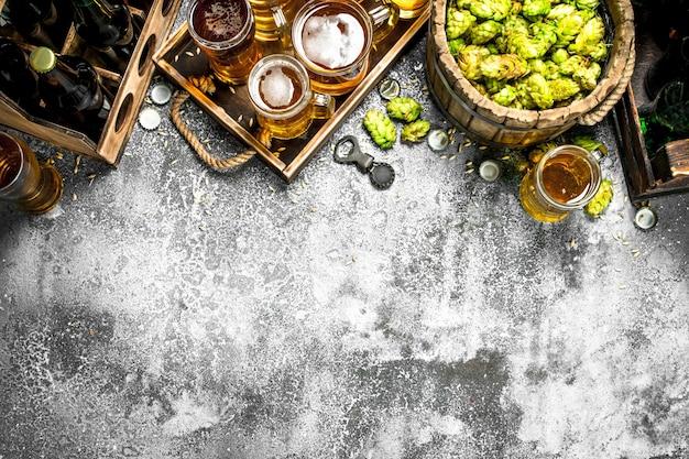 Пивной фон. свежее пиво с ингредиентами. на деревенском фоне.