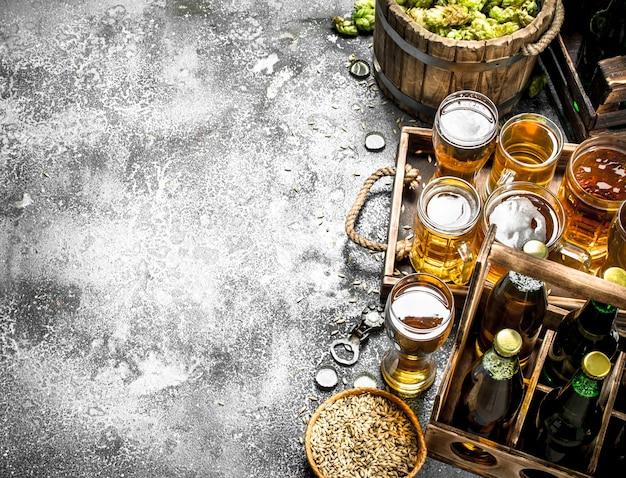 맥주 배경. 시골 풍 테이블에 재료와 신선한 맥주입니다.
