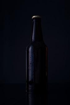 Бутылка пива на черном фоне бутылка пива на черном фоне. рекламное фото