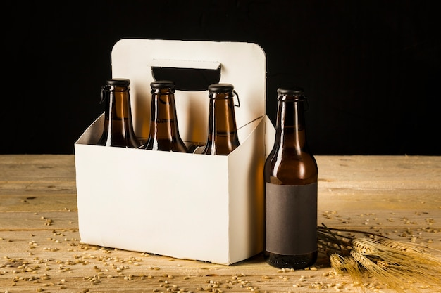 Beer bottle carton box and ears of wheat on wooden surface