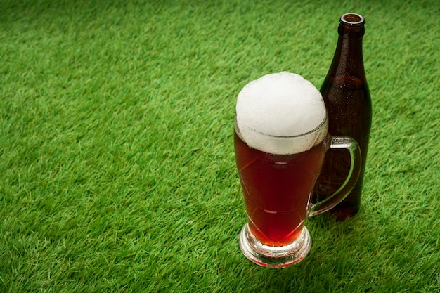 Beer bottle and glass on grass with copy space