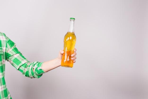 白い背景の上の手でビール瓶。