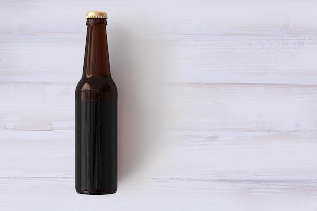 나무 배경에 빈 레이블이 있는 맥주 병 모형. 옥토버 페스트 개념입니다.