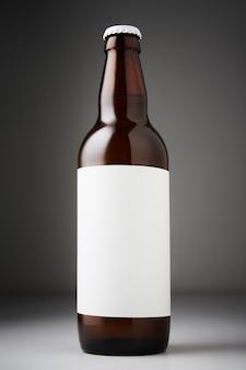 맥주 병 모형. 어두운 배경에 빈 레이블이 있는 라거 맥주 한 병