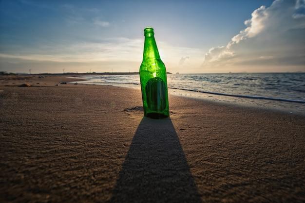 맑은 하늘과 모래 해변에서 맥주 병