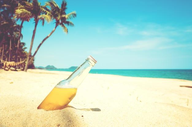 야자수와 모래 해변에서 맥주 병. 빈티지 색조 효과