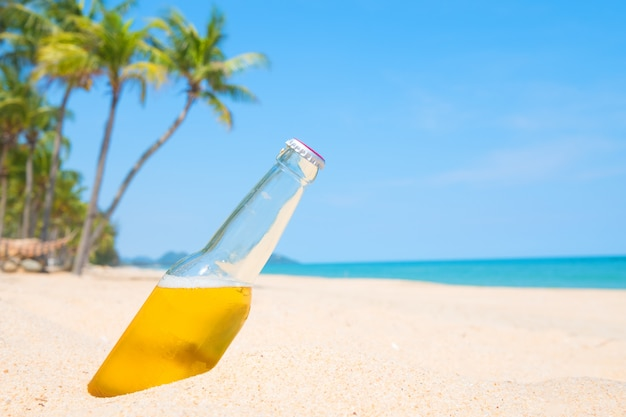 야자수와 모래 해변에서 맥주 병