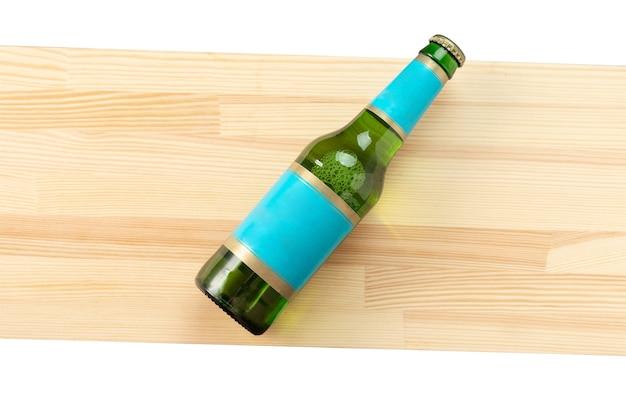 Бутылка пива на деревянной доске - вид сверху
