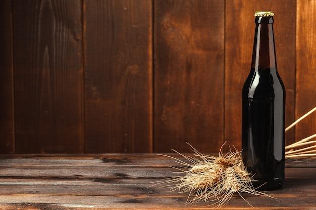 Пивная бутылка на деревянной стене с copyspace