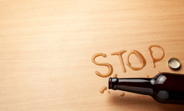 Beer bottle and spilled beer in the shape of the word stop. ban alcohol.