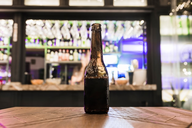 Beer bottle without cap on wooden table in the bar