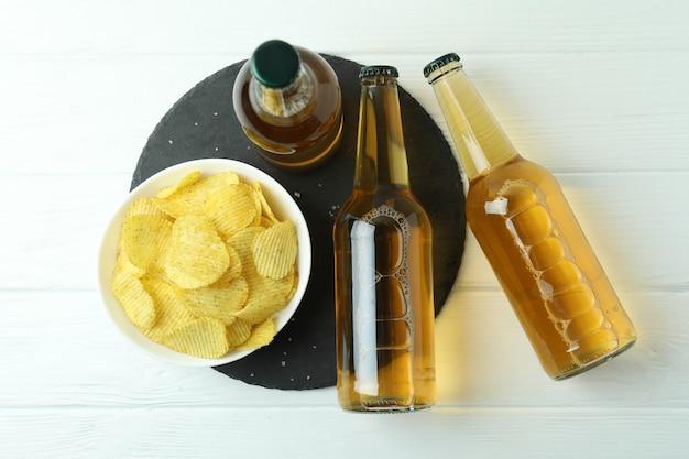 ビール瓶と白い木製の背景にチップ