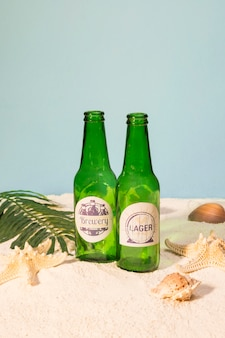 Beer bottles on beach with shells