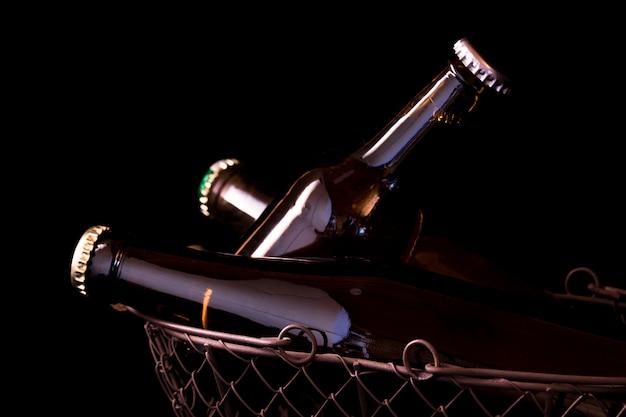 Beer bottles on a black background chiaroscuro in an old metal mesh basket