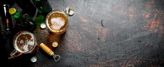 Beer in bottles and glasses. on rustic background
