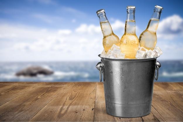 ビーチの背景に氷のビール瓶