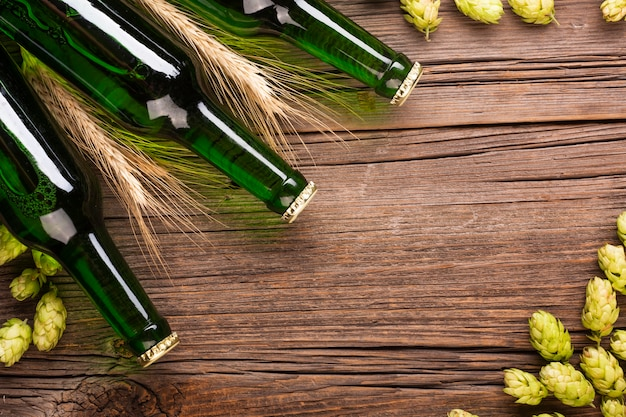 Beer bottles and ingredients of beer on wooden background