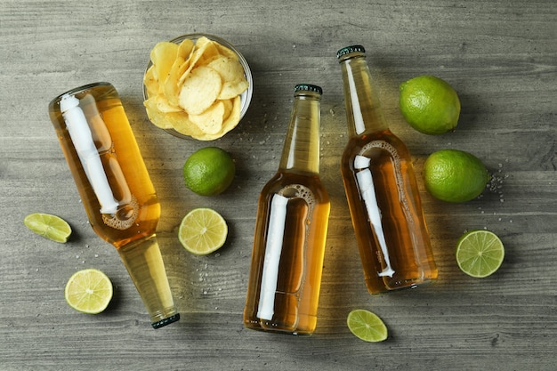 Beer bottles and snacks on gray textured background